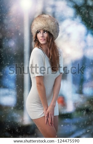 Attractive young woman in a winter fashion shot.Winter wild girl on snow.Winter Girl with beautiful make up, and snow flake, forest background.Portrait of sexy woman