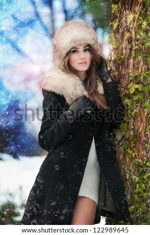 attractive young woman in a winter fashion shot.Winter wild woman on snow.Winter Girl with beautiful make up,  and snow flake, forest background.Portrait of attractive