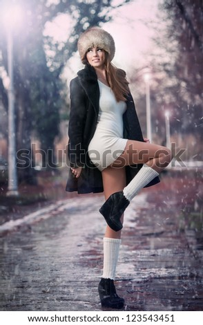 attractive young woman in a winter fashion shot.Winter wild woman on snow.Winter Girl with beautiful make up, and snow flake, forest background.Portrait of attractive woman