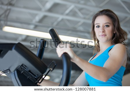 Attractive young woman in Blue at the Gym on stair steppers