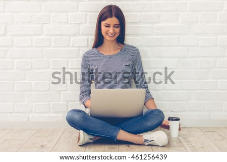 Attractive young woman in casual clothes is using a laptop, holding a cup of coffee and smiling while sitting on the floor in front of white wall #461256439