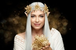 Attractive young woman in elf queen costume smiling for camera and holding golden blossom on hans against sparks during carnival