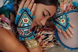 attractive young woman in ethnic jewelry with drum. close up portrait.