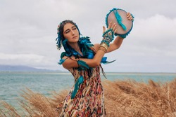 attractive young woman in ethnic jewelry with drum outdoors