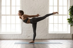 Attractive young woman in grey sportswear, leggings and bra practicing yoga, beautiful girl standing in Warrior three, Virabhadrasana pose, working out at home or in yoga studio with white walls