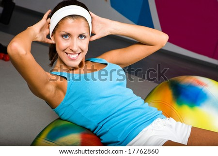 Attractive young woman in health club with pilates ball