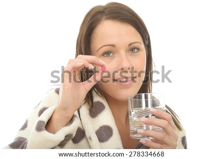 Attractive Young Woman In Her Warm Cosy Dressing Gown Feeling Poorly and Unwell Taking Medicine