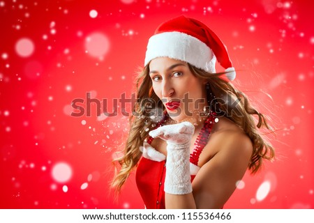 Attractive young woman in Santa Claus costume blowing snow flakes on isolated red background Xmas celebration