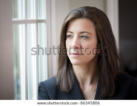 Attractive young woman in suit looking out of window #86345806