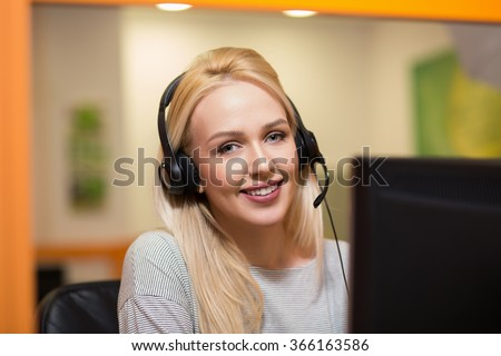 Attractive young woman in suit sitting at call center office and working.