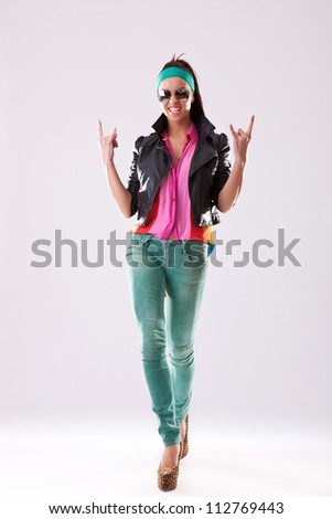 Attractive young woman in sunglasses high heels and casual clothes making the rock and roll hands gesture
