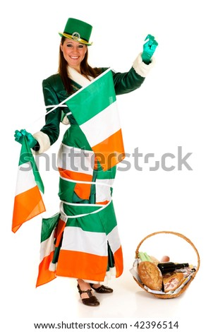 Attractive young woman in traditional St Patrick holiday outfit, food basket in front, Irish and american banner flags in back. Studio shot.
