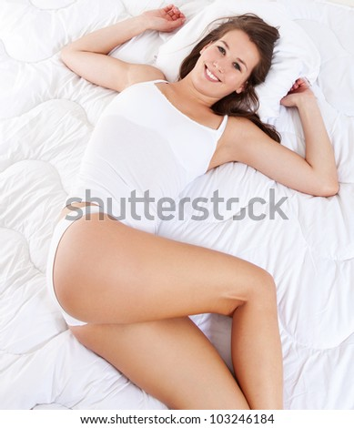 Attractive young woman in underwear lying on blanket. All on white background.