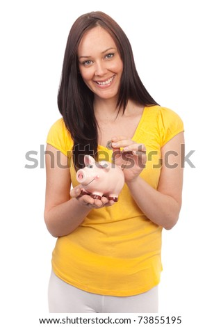 Attractive young woman inserting coins in a piggy bank on white background