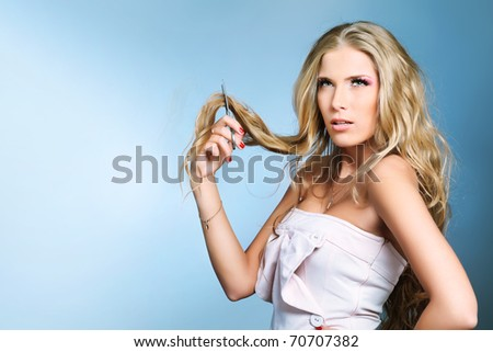 Attractive young woman is cutting her own hair. Studio shot over grey background.