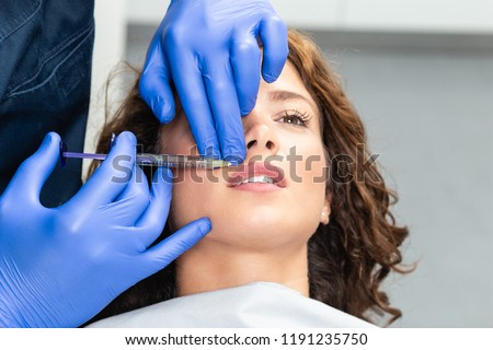 Attractive young woman is getting a rejuvenating facial injections. She is sitting calmly at clinic. The expert beautician is filling female wrinkles by hyaluronic acid. #1191235750