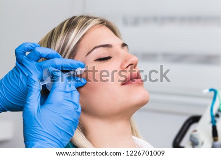 Attractive young woman is getting a rejuvenating facial injections. She is sitting calmly at clinic. The expert beautician is filling female wrinkles by hyaluronic acid.