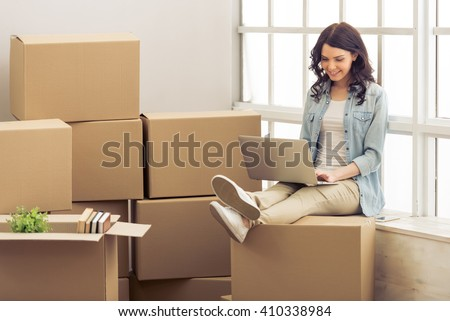 Attractive young woman is moving, sitting among cardboard boxes, using a laptop and smiling