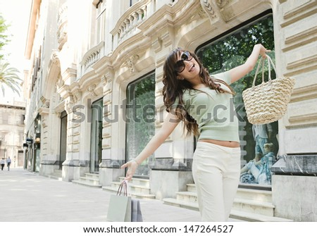 Attractive young woman joyfully walking down a shopping street in a classic city, holding shopping bags up with her arms and smiling at the camera.