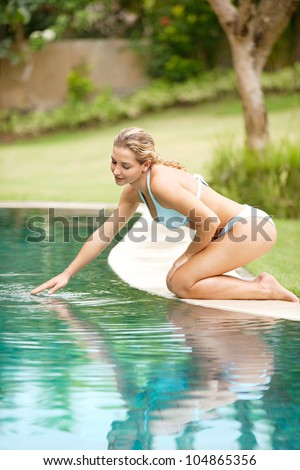 Attractive young woman kneeling by the edge of a swimming pool, touching the calm water with her hand.