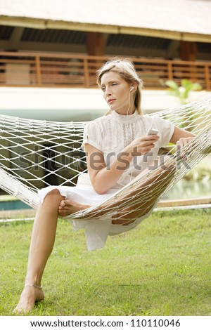 Attractive young woman listening to music while sitting on a hammock on vacation, in a tropical destination hotel\'s garden.