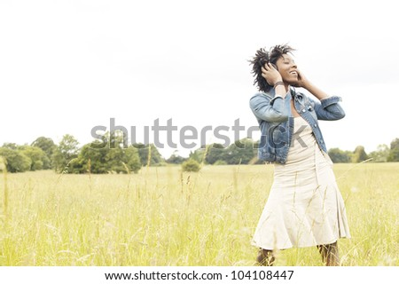 Attractive young woman listening to music with headphones in an open field, dancing and singing.