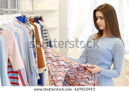 Attractive young woman looking disappointed and unhappy choosing dresses at the clothing store poor quality not impressed shopping fashion negativity sales retail consumerism customer client service