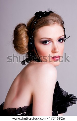 Attractive young woman looking over her shoulder. She is wearing black feather and pearl hair dressings. Vertical shot.