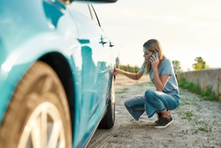 Attractive young woman looking sad, calling car service, assistance or tow truck while having troubles with her auto, checking wheel after car breakdown on local road side, Horizontal shot