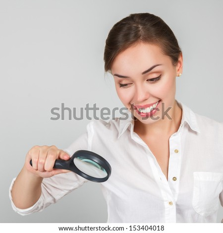 Attractive young woman looking through a magnifying glass