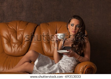 Attractive young woman lying on a leather sofa with cup of coffee.