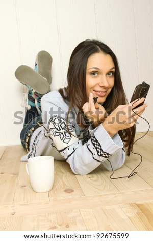 Attractive young woman lying on the floor at home listening to the radio. Listening to music