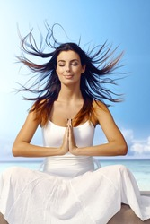 Attractive young woman meditating on the beach eyes closed, wind blowing hair, smiling, sitting in prayer position.