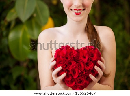 Attractive young woman naked in a green lush garden holding a red roses heart in front of her chest, wearing red lipstick, smiling.