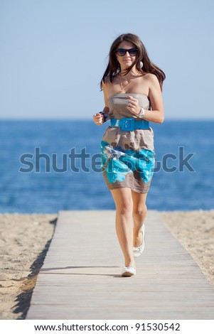 Attractive young woman on the beach. Attractive young woman in dress and sunglasses running along the beach