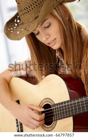 Attractive young woman playing guitar with joy, wearing western hat.?