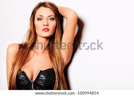 Attractive young woman posing by the wall.