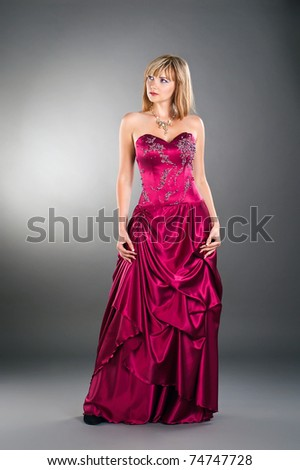 attractive young woman posing on studio neutral background wearing purple gown