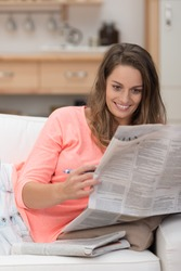Attractive young woman reading the newspaper with a smile and holding a pencil in her hand to mark any adverts of interest