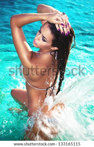 attractive young woman refresh in pool under the small waterfall