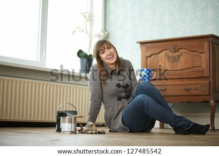 Attractive young woman relaxing at home with cup of tea
