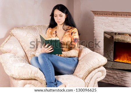 Attractive young woman relaxing in a comfortable armchair reading a book near the blazing fire