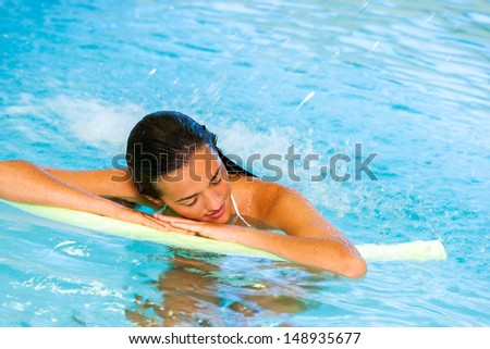Attractive young woman relaxing under cascade in spa pool.
