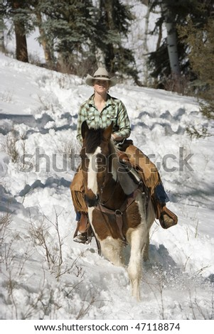 Attractive young woman riding a horse in the snow. Vertical shot.