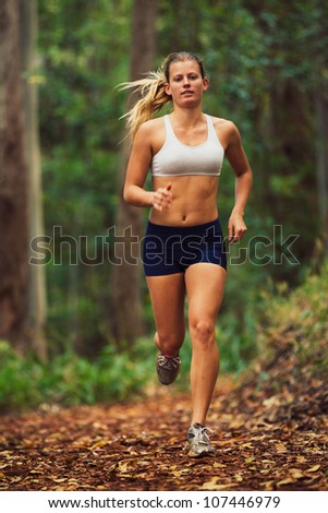 Attractive Young Woman Running in the Forest