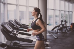 Attractive young woman runs on a treadmill is engaged in fitness sport club