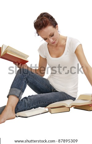 Attractive young woman seated on the floor doing research in old books.