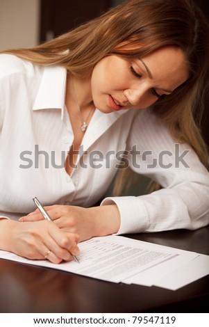 Attractive young woman signing contract