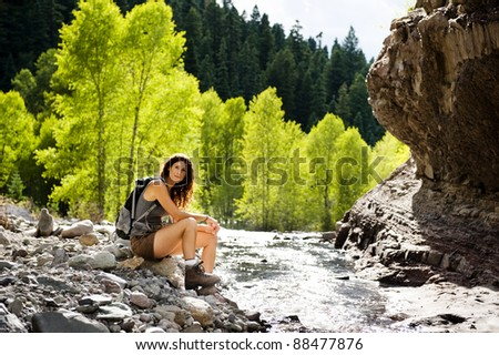 attractive young woman sitting by a mountain stream