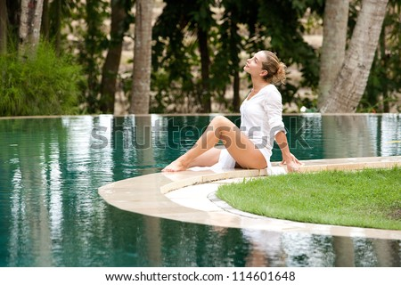 Attractive young woman sitting down at the edge of a swimming pool, relaxing in a tropical garden.